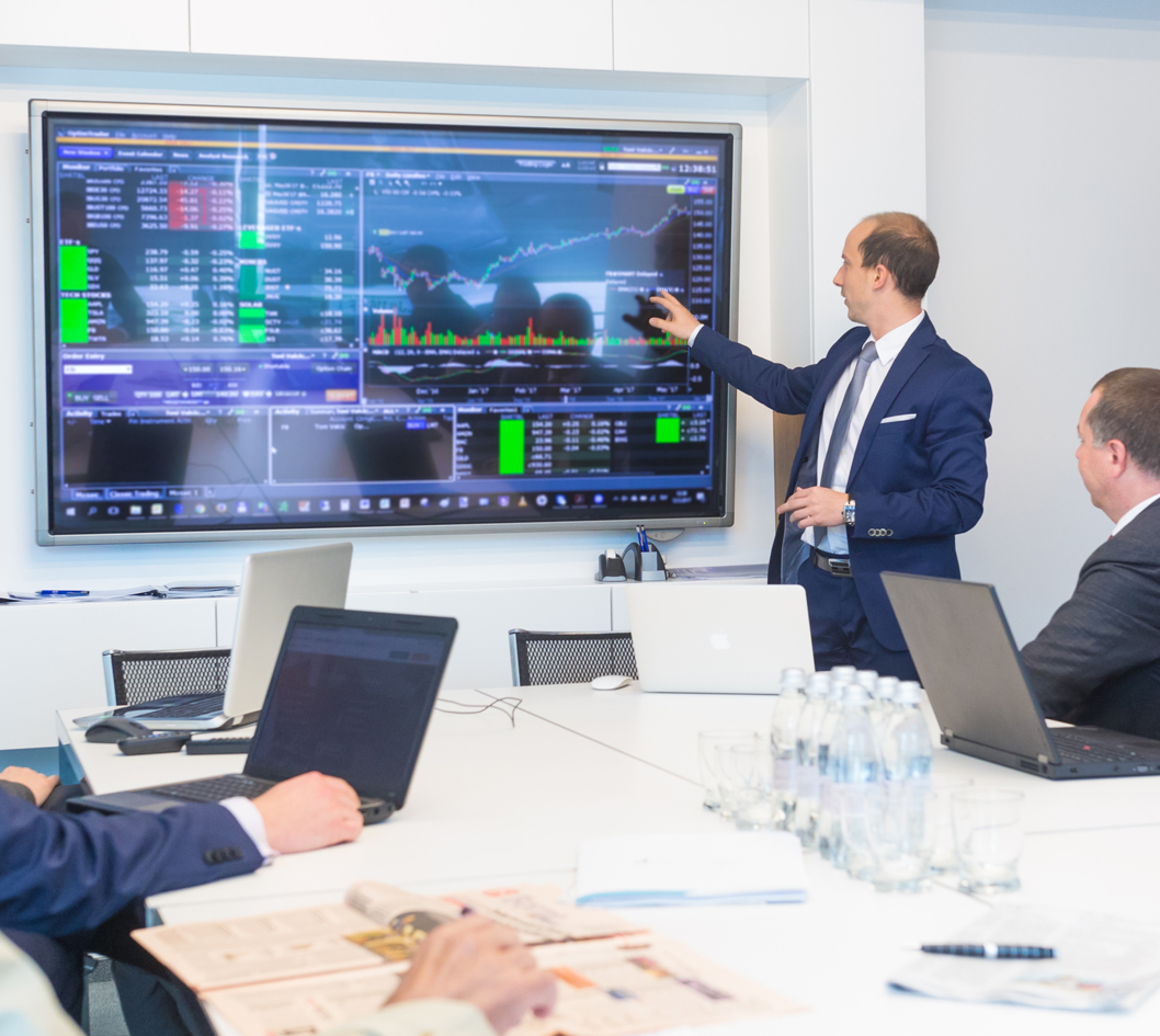 advisors reviewing market data on big screen